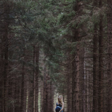 gravid kvinna i mork skog